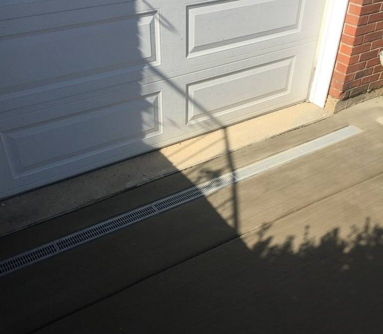 Garage concrete apron with drain installation by EDMAR Corporation Masonry